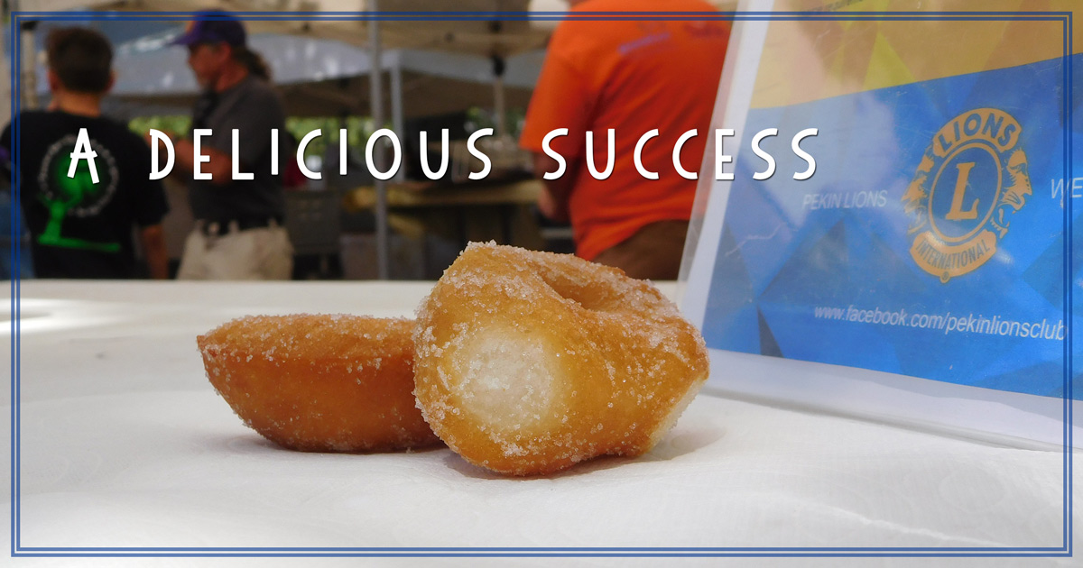 "A picture of two donuts in front of a sign with the Lions Club logo and Lions working in the background with the title words ""A Delicious Success"""