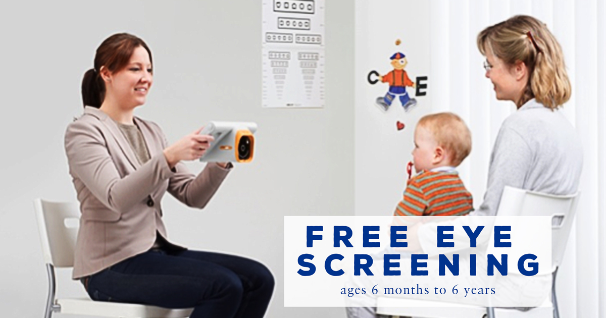 Mother holding toddler boy on her lap facing another woman holding the plusoptix mobile camera for a vision screening